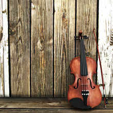 Violin Leaning On A Wooden Fence. Room For Text Or Copy Space.