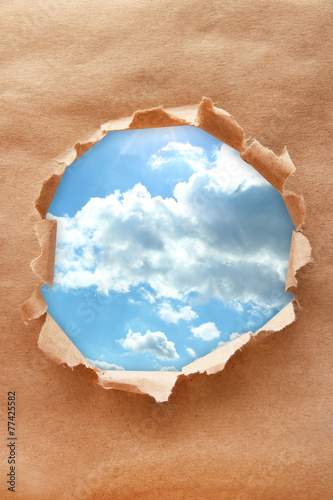 Blue sky background with clouds through hole in craft paper