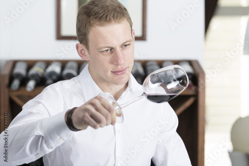 Fotografía  man analyzing a red wine glass.
