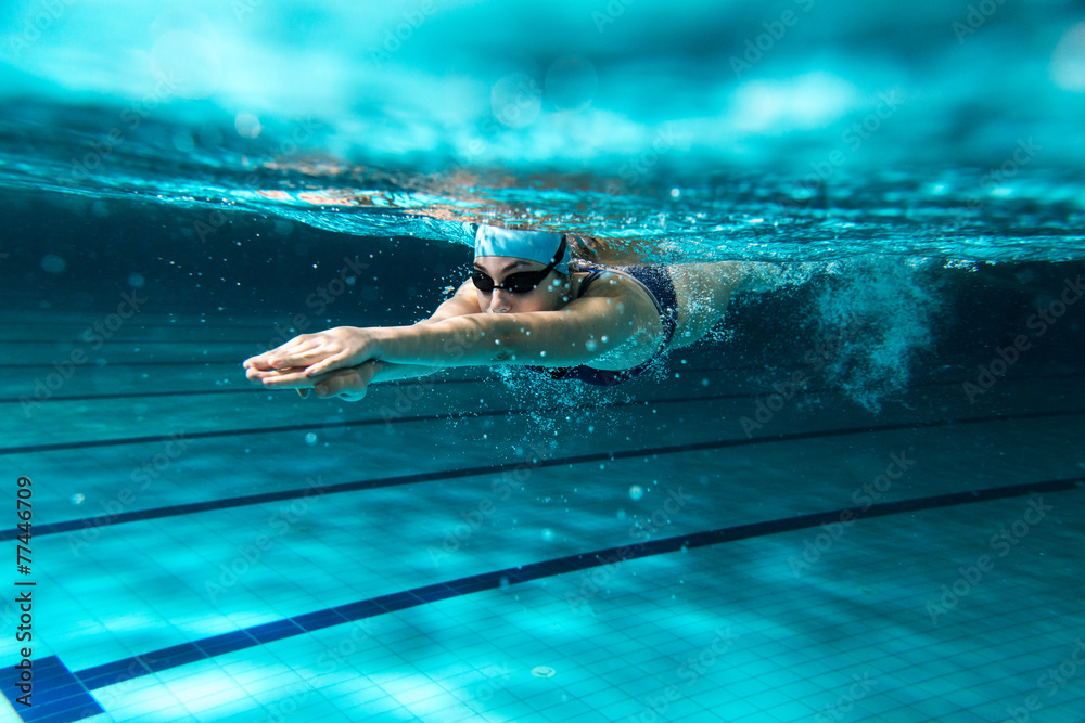 Fototapeta Female swimmer at the swimming pool.Underwater photo.