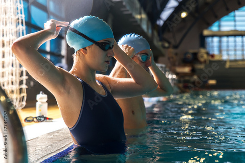 Photo  Two swimmers preparing to race at the swimming pool.