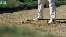 Shot Of A Man Golfer On A Sand Golf Course Preparing For Hits