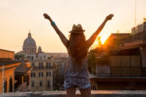 Fotografía Young woman looking on rooftops of rome on sunset and rejoicing.