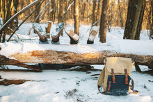 Couple Laying On The Ground In Winter Forest With Legs On The Tr