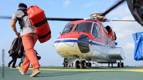 Deurstickers Helicopter passenger carry his baggage to embark helicopter at oil rig plat