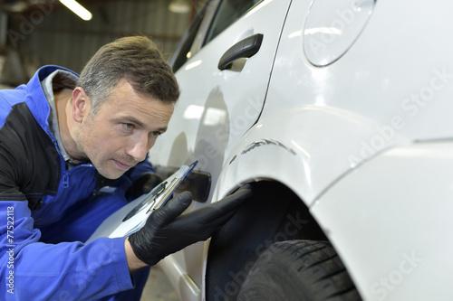 Mechanic checking on auto bodywork Canvas Print