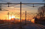 Trains leaving a station during a winter sunrise.