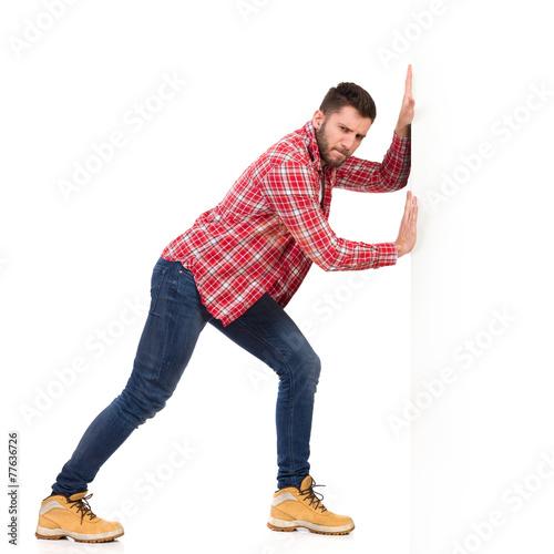 Fotografía Man pushing a white wall