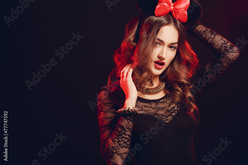 Photo  Portrait of a beautiful model with a red bow on a dark backgroun