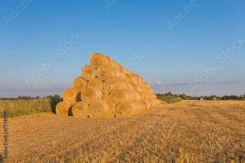 Foto op Aluminium Blauw Piled hay bales on a field against blue sky
