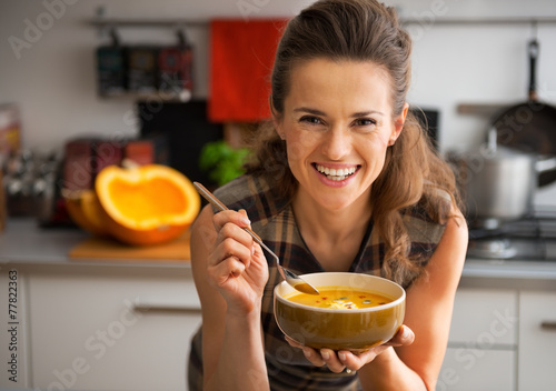 Leinwand Poster Happy young woman eating pumpkin soup in kitchen