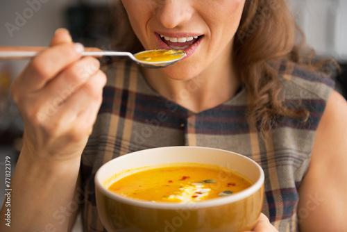 Fotografie, Obraz  Closeup on young woman eating pumpkin soup in kitchen