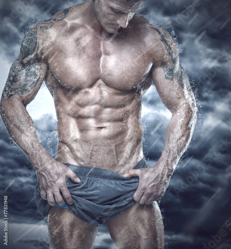 Muscular man showing his body in stormy weather Canvas Print