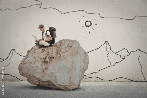Foto op Canvas Fantasie Landschap Explorer sitting on top of a rock