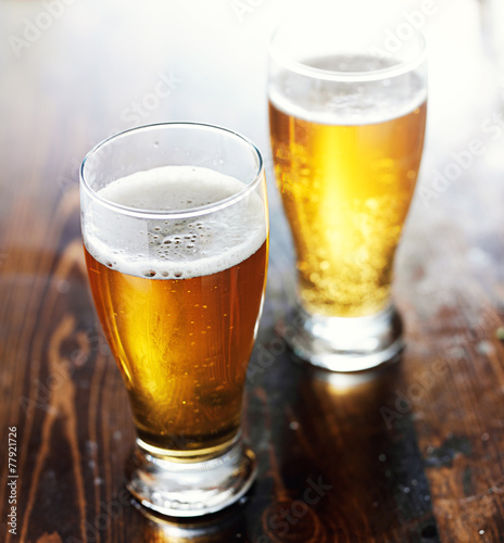 Fotografia  fresgly poured beer in mugs on top of wooden table