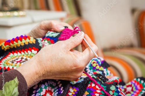Fotografie, Obraz  Hands of woman knitting a vintage wool quilt