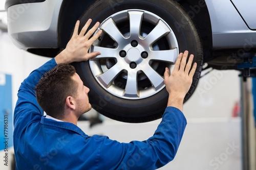 Fotografie, Obraz  Mechanic adjusting the tire wheel