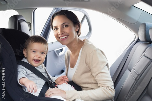 Fotografia, Obraz  Mother securing her baby in the car seat