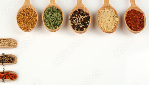 Different spices and herbs in wooden spoons isolated on white