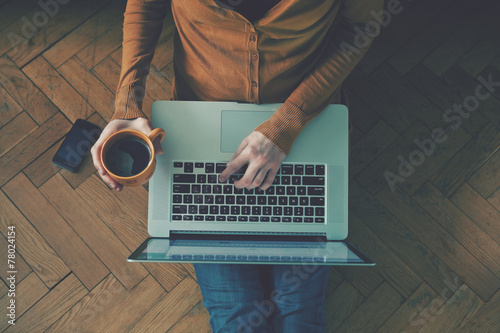 Fotografia  Laptop and coffee cup in girl's hands sitting on a wooden floor