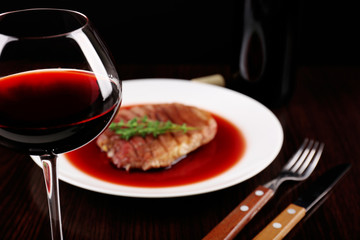 Fototapeta Do steakhouse Glass of wine with grilled steak in wine sauce