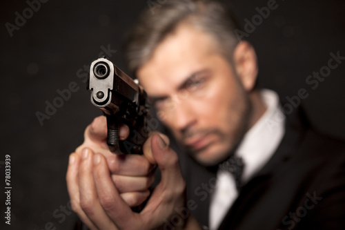 handsome man in a suit aim with a gun плакат