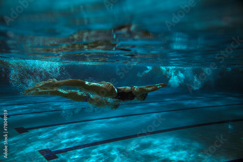 Swimmers.Underwater image.Grain effect added. Canvas Print