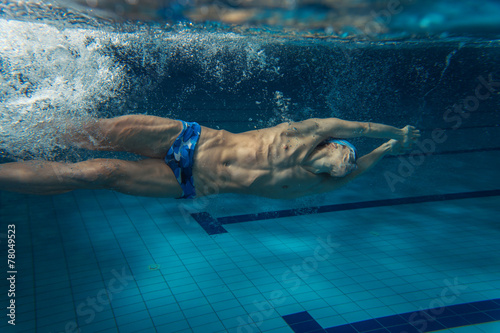 Photo  Male swimmer at the swimming pool.Underwater photo.