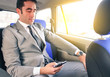 Young handsome businessman sitting in taxi cab while texting sms