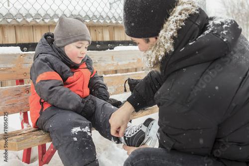 Plakat Rodzina grająca na lodowisku zimą.
