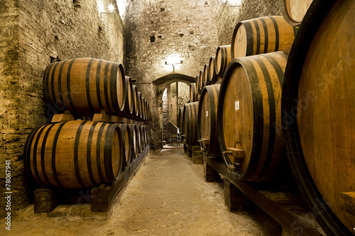 Fotografia  Wine barrels stacked in the old cellar of the winery