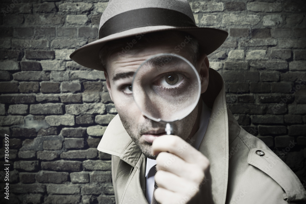 Fototapeta Vintage detective looking through a magnifier