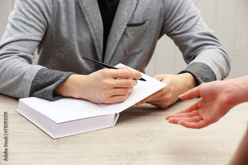 Photo  Author signing autograph in own book at wooden table