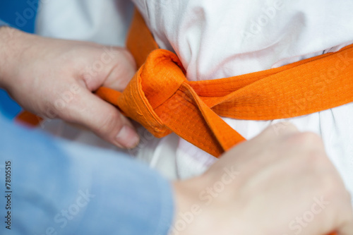 Garden Poster Martial arts Father ties an orange belt on his son's martial arts uniform