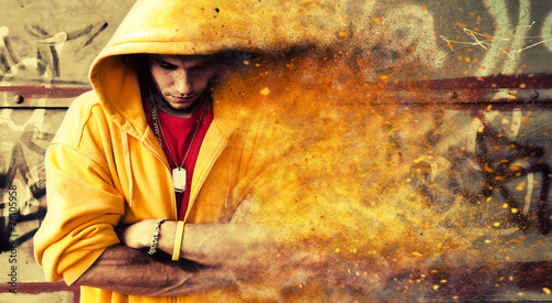 Young man in hooded sweatshirt on grunge wall. Particles effect