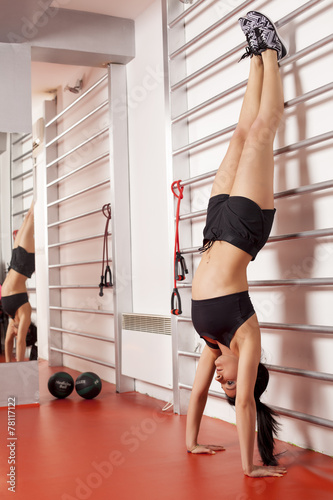 pretty young woman doing a handstand next to bars Fototapeta