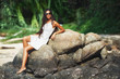 beautiful tanned woman sitting on stone