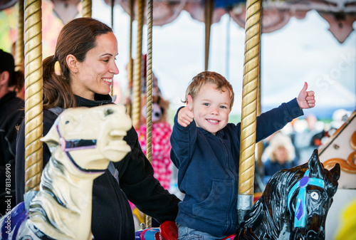 Foto op Plexiglas Amusementspark Boy with Two Thumbs Up with Mother on Carousel
