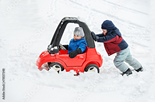 Fotografie, Obraz  Young Boy Gives a Push to his Brother's Car Stuck in the Snow