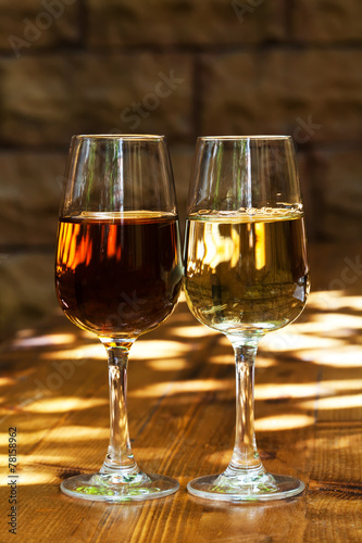 Two glasses of sherry on a wooden table.