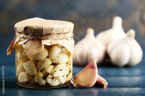 Fototapeta Canned garlic in glass jar on color wooden background obraz