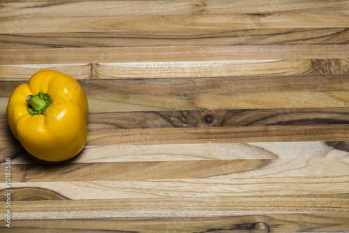 Fotografie, Obraz  Yellow Pepper on a teak cutting board