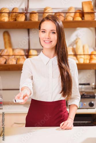 Foto op Plexiglas Bakkerij Beautiful young saleswoman in a bakery