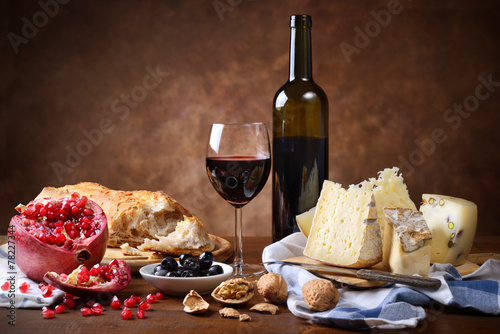 Fényképezés  Red wine, cheese, walnuts, olives, pomegranate and bread