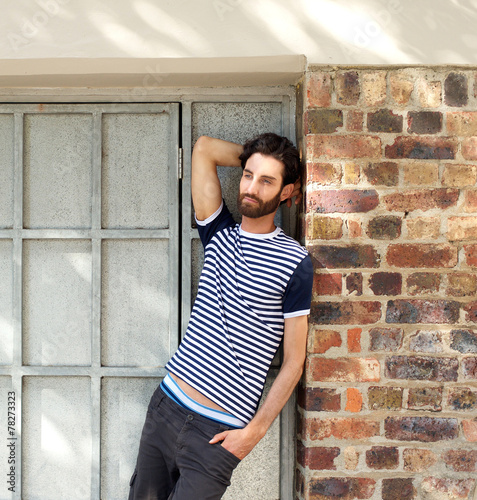 Fotografía  Young man with beard leaning against wall outdoors
