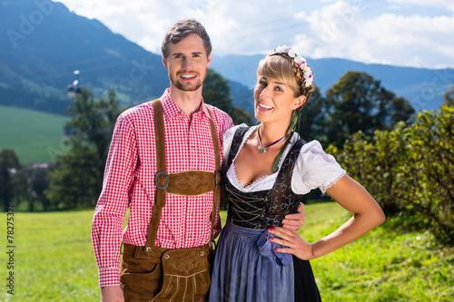 Fotografie, Obraz  Paar in Tracht steht auf Alm in den Alpen