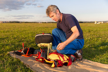 Man Puts  Bag With Parachute In   Knapsack Outdoor
