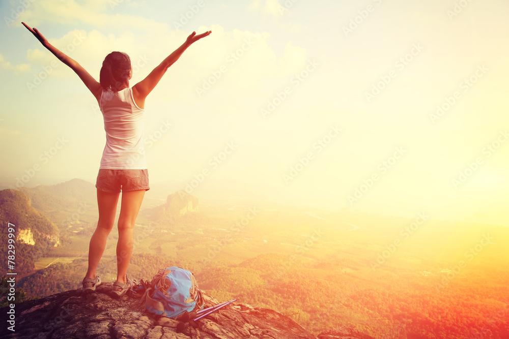 Fototapeta strong confident woman hiker open arms at on mountain peak rock