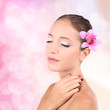 Beautiful young woman with pink flower in hair