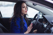 woman looks pensively into the windshield of the car